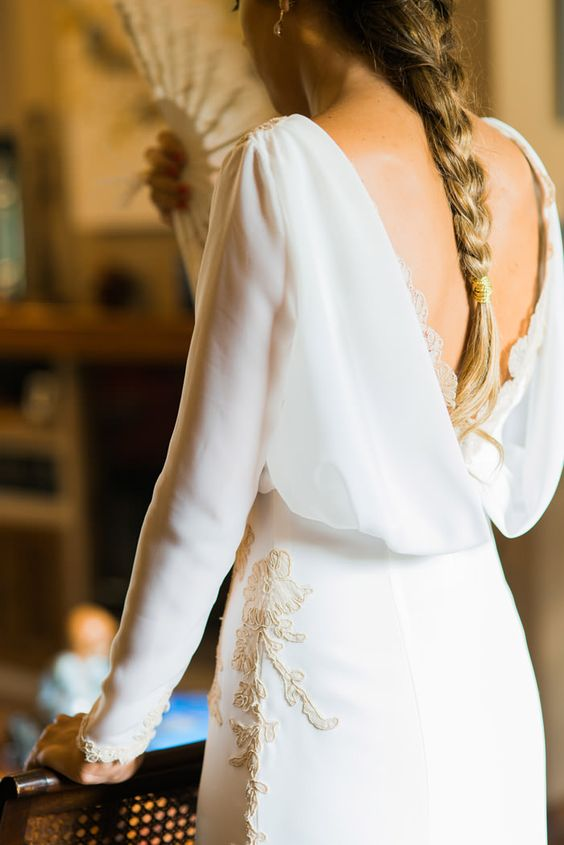 a refined modern plain sheath wedding dress with an open back with lace and gold lace appliques is a very chic idea