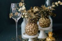 a refined moody tropical wedding tablescape with gilded pineapples, white porcelain, gilded leaves and gold leaf on the table