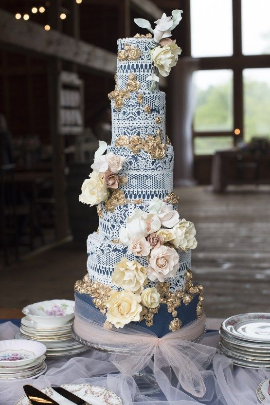 a refined navy and white lace wedding cake with gold detailing, neutral and blush sugar blooms looks wow