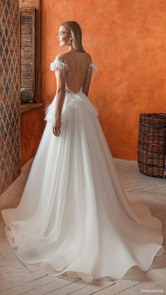 a refined princess-style wedding dress with a fringe and lace applique boidce, a low back and a layered full skirt witha train for a formal wedding