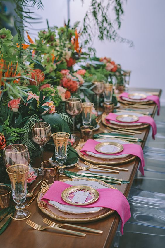 a refined tropical wedding tablescape with greenery, leaves and bold blooms, pink napkins and gold cutlery, gold rim glasses and plates
