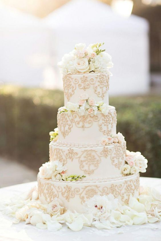 a refined white wedding cake with gold patterns and fresh white blooms and greenery on top