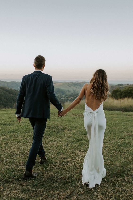 a relaxed and flowy sheath wedding dress with a low back on spaghetti straps, a sash and a slight train for a modern bride