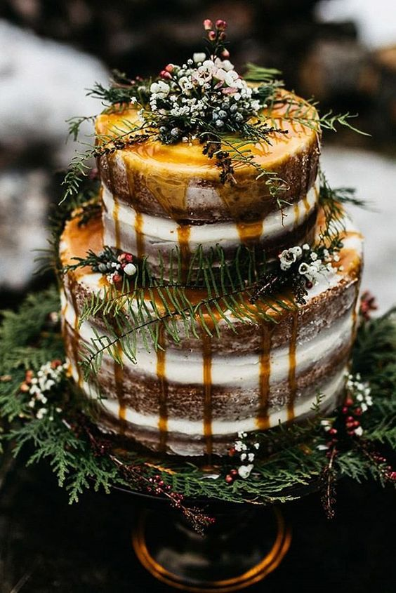 a relaxed woodland wedding cake, a demi naked one with caramel drip, greenery, berries and blooms