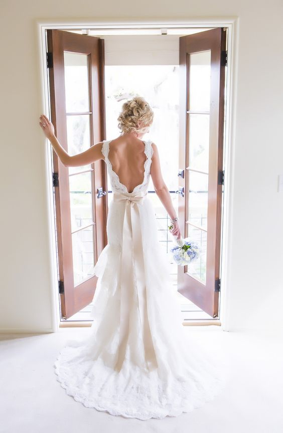 a romantic lace A-line wedding dress with a low back and a skirt with a train plus a bow on the back is a gorgeous vintage option