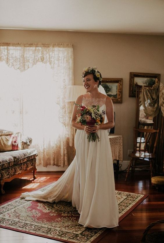 a romantic wedding dress with a lace bodice and an illusion neckline plus a pleated skirt with a train