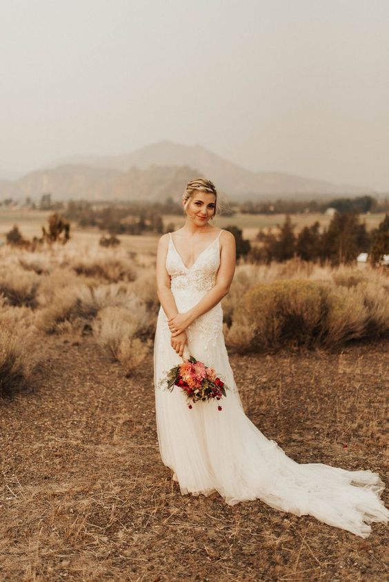 a romantic wedding dress with a lace bodice on spaghetti straps and a V-nekcline plus a train