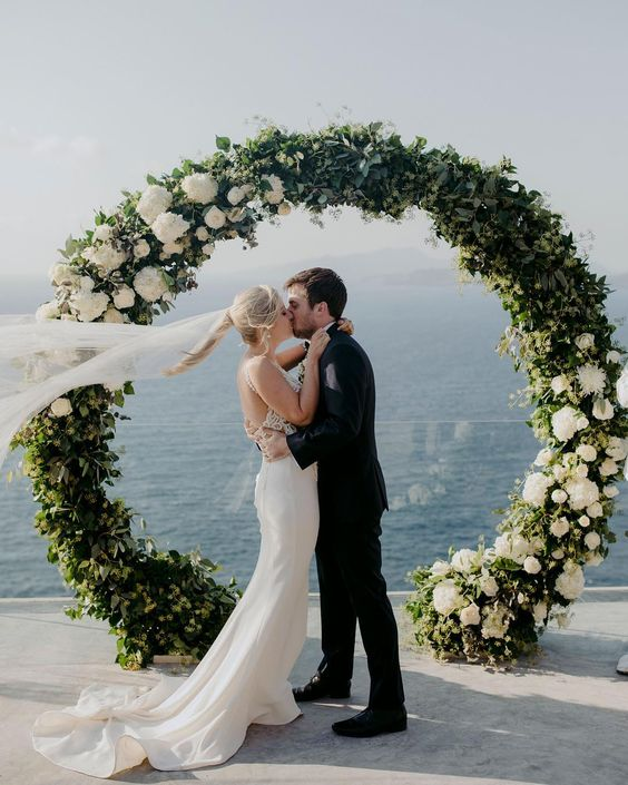 a round wedding arch decorated with greenery and white blooms plus a sea view for a breathtaking wedding ceremony