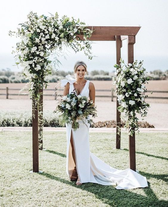 a rustic wedding arch decorated with greenery and white blooms is a cool idea for a modern wedding