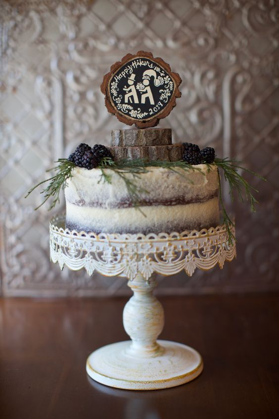 a semi naked chocolate wedding cake topped with greenery, berries, wood slices and a chalkboard topper