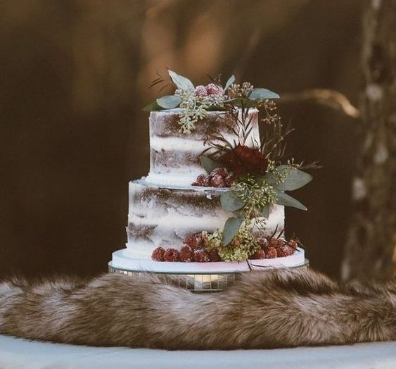 a semi naked wedding cake topped with fresh eucalyptus and roses and with berries for a forest wedding