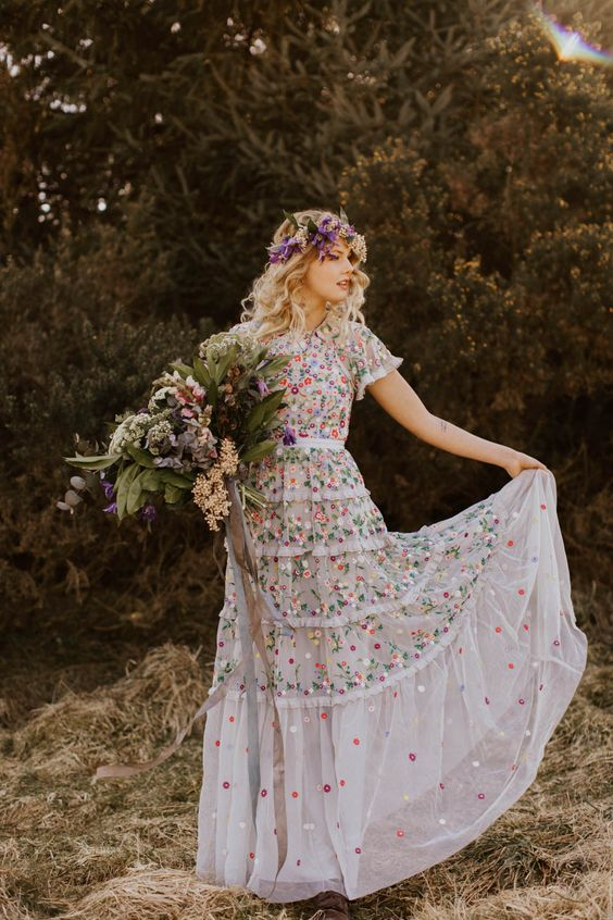 a sheath wedding dress with short sleeves and a high neckline plus gorgeous colorful florla embroidery and a bright floral crown