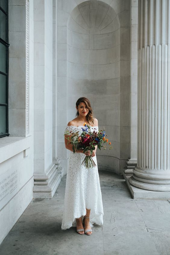a simple and beautiful off the shoulder boho lace high low wedding dress with a train for a summer boho bride