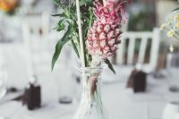 a simple and cute wedding table decoration – a crystal vase with blooms, a pink pineapple and a flag for a tropical wedding