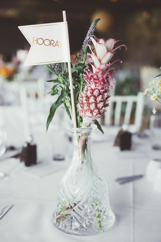 a simple and cute wedding table decoration - a crystal vase with blooms, a pink pineapple and a flag for a tropical wedding
