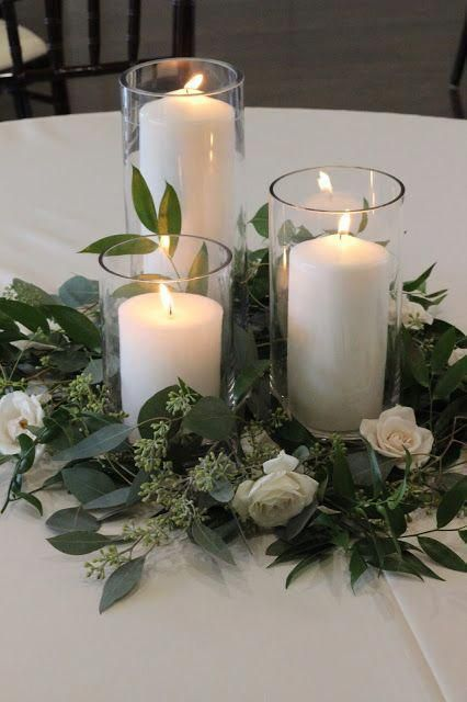a simple wedding centerpiece of greenery, white blooms and white pillar candles will fit many wedding styles