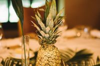a simple wedding centerpiece of tropical foliage, a gilded pineapple, a bud vase with a leaf, a gilded candleholder and some photos