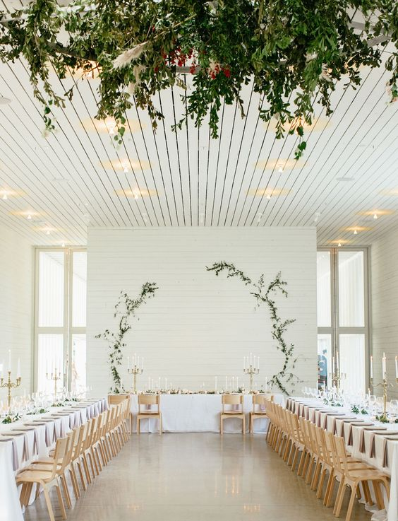 a simple white wall with greenery branches to form a circle is a cool idea, add a matching chandelier