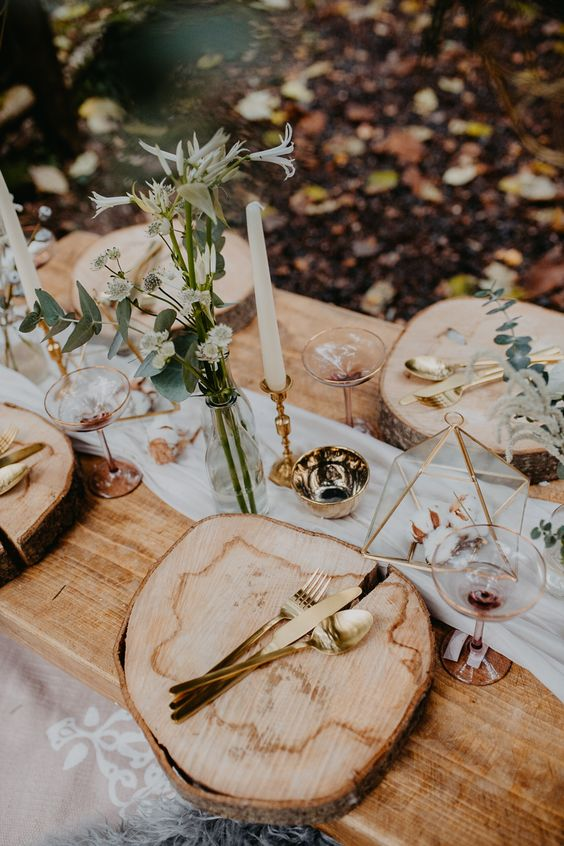 a simple woodland wedding table setting with wood slices, simple wildflowers and touches of gold here and there