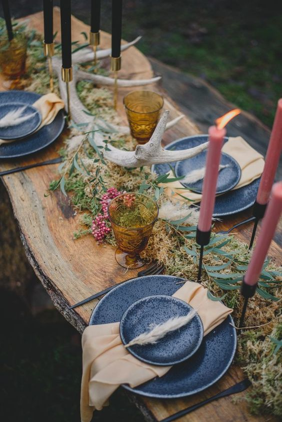 a simple woodland wedding table with dried herbs, berries, antlers, colored candles and grey plates