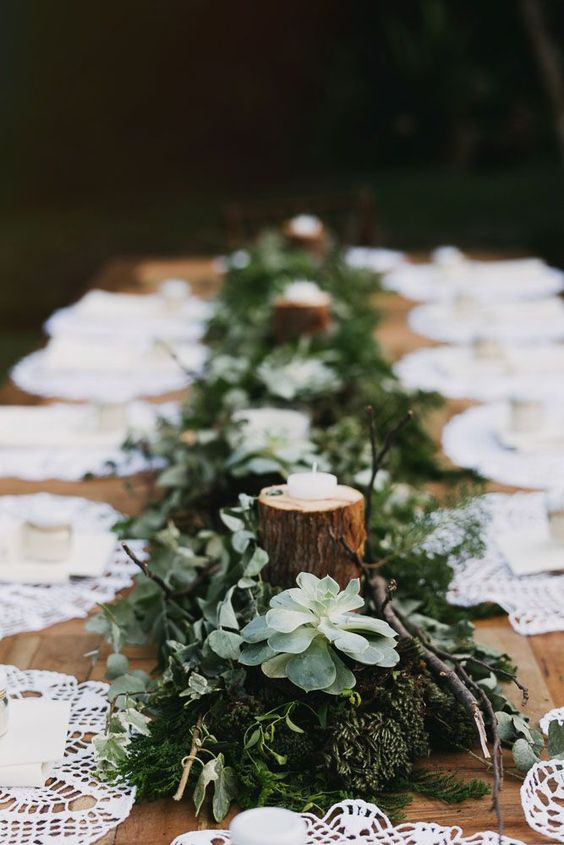 a simple woodland wedding tablescape with a runner made of moss, greenery, succulents and tree branches with candles