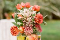 a square glass vase with apples, pears, bold blooms and a pink pineapple is a lovely and easy bright wedding centerpiece