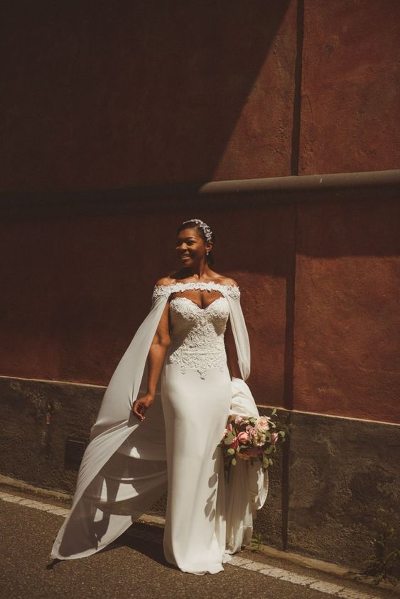 a statement strapless wedding dress with a lace bodice and a plain skirt, a capelet with lace and an embellished headpiece