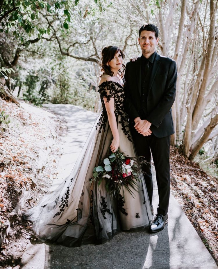 a stunning off the shoulder A-line wedding dress with black lace appliques and embellishments plus a train for a Halloween wedding