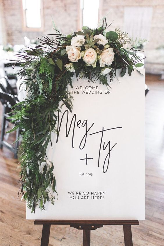 a stylish modern wedding sign with lots of textural greenery and neutral blooms can be DIYed