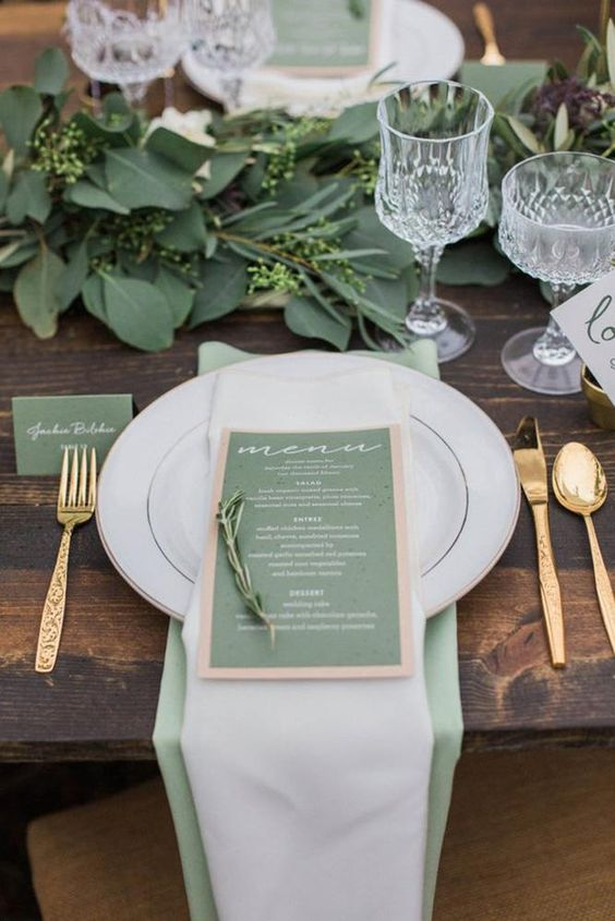 a stylish wedding tablescape done in green, gold and white, with a leafy runner and a green and copper menu