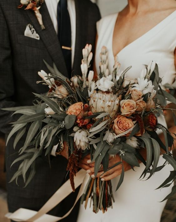 a summer or fall boho wedding bouquet of rust-colored blooms, white blooms and lots of greenery