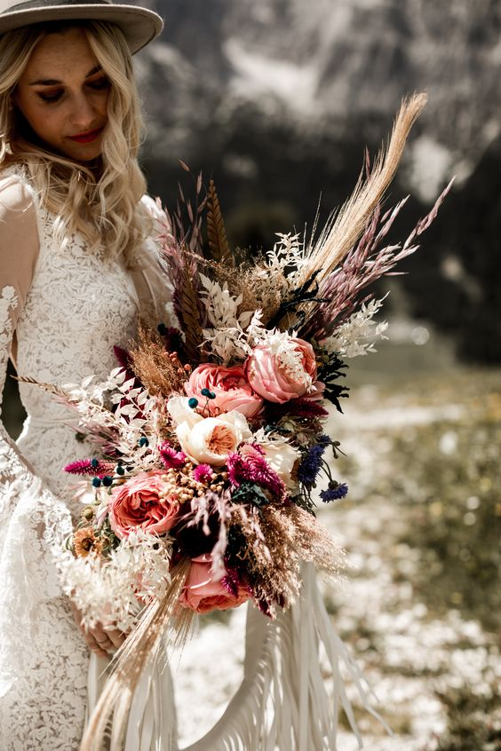 a summer wedding bouquet of pink and blush blooms, berries, white grasses and leaves for a boho bride