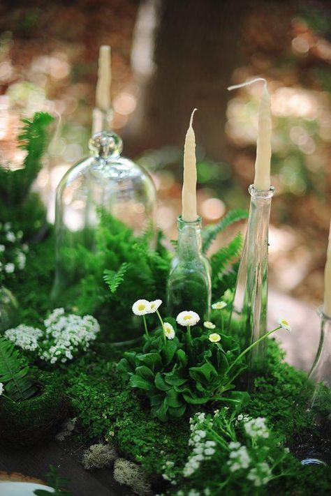 a summer woodland wedding centerpiece of lush greenery, white blooms and candles in glass bottles