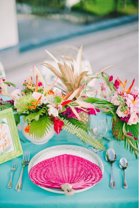 a super bold wedding tablescape with a turquoise tablecloth, a pink fan, bright blooms and leaves and a sign in a green frame