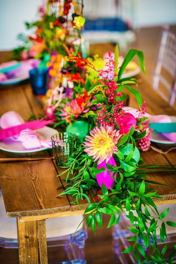 a super bold wedding tablescape with bright napkins, a greenery and bright flower table runner is wow