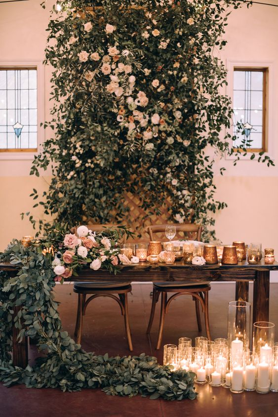a super lush greenery and blush blooms reception backdrop plus a table runner and lots of candles