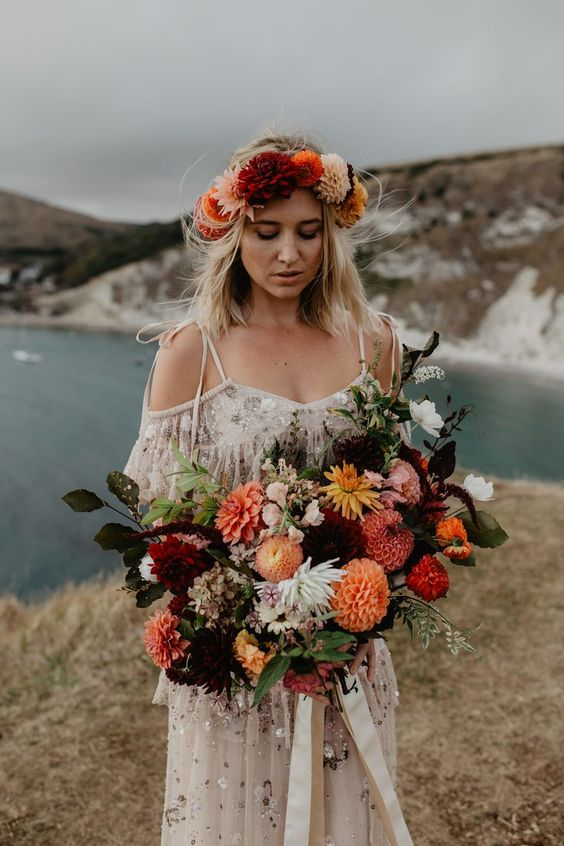 a supmtuous fall boho wedding bouquet of deep purple, orange, red and white blooms, greenery and dark leaves