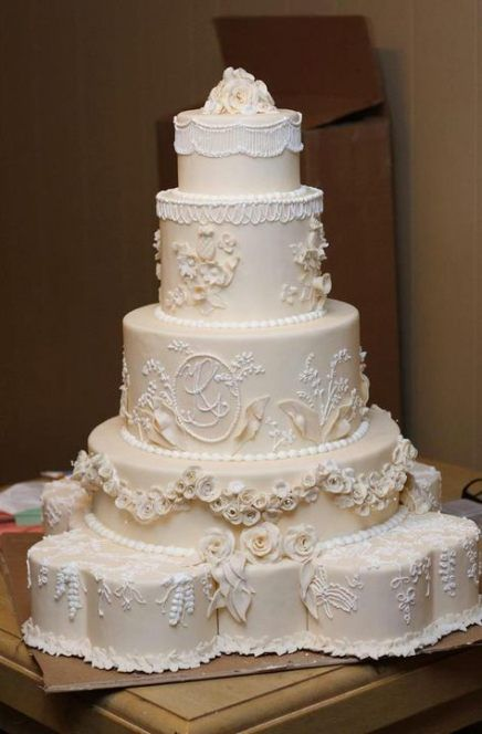 a tan wedding cake with floral patterns and lace plus fringe on top is a very refined idea