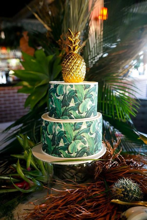 a tropical leaf print wedding cake with a gilded pineapple on top is a very bright and cool idea for a modern bold wedding
