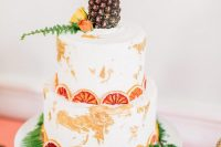 a tropical wedding cake with dried citrus slices, ferns, a mini pineapple on top is a fun and cool idea