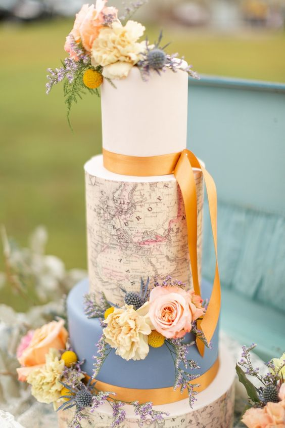 a vintage-inspired wedding cake with a blue and white tier, with a map tier and natural blooms and marigold ribbons