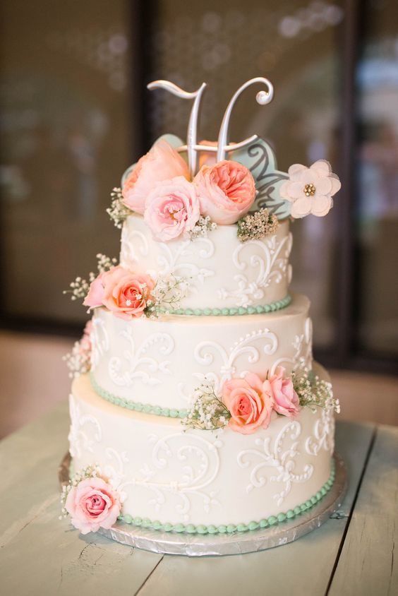 a vintage-inspired white wedding cake with patterns, pink blooms and baby's breath and a metallic monogram