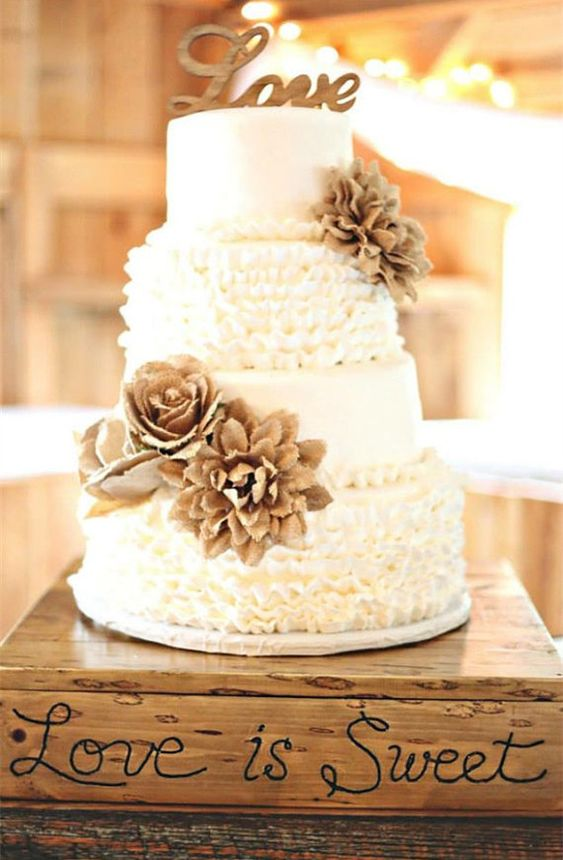 a vintage rustic wedding cake with sleek and ruffled tiers, burlap blooms and a wooden topper