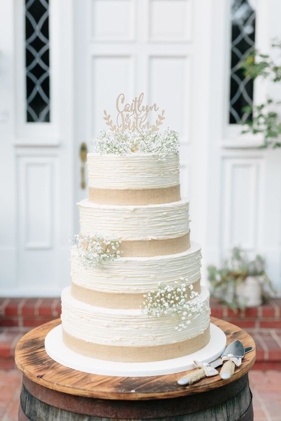 a vintage rustic wedding cake with textural tiers, burlap ribbons and baby's breath plus a chic topper