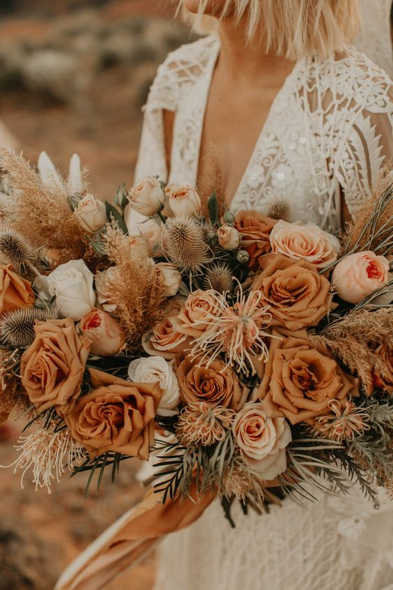 a warm-colored rust wedding bouquet with white blooms, dried touches and greenery for a desert boho bride
