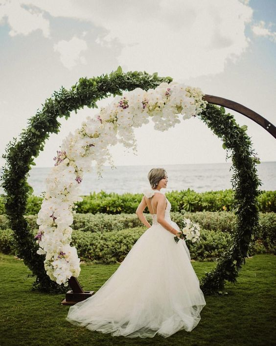 a wedding altar made of two rings covered with  greenery and lush white orchids for a luxurious look