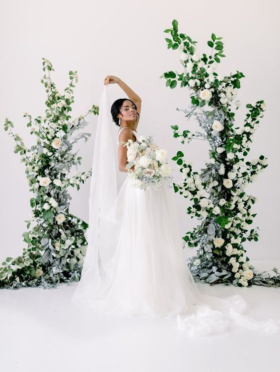a wedding altar of greenery and white blooms is a chic statement decor idea