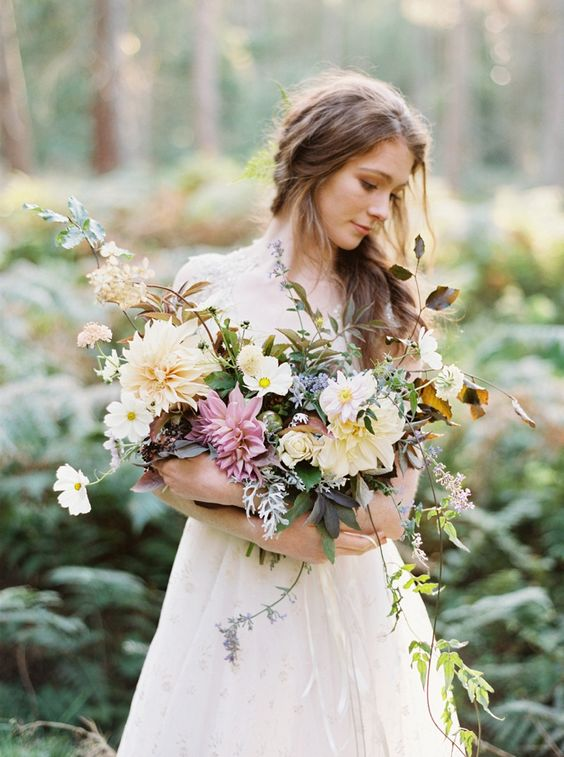 a whimsical wedding bouquet with large scale blooms in pastel shades and usual and dark greenery for a spring wedding