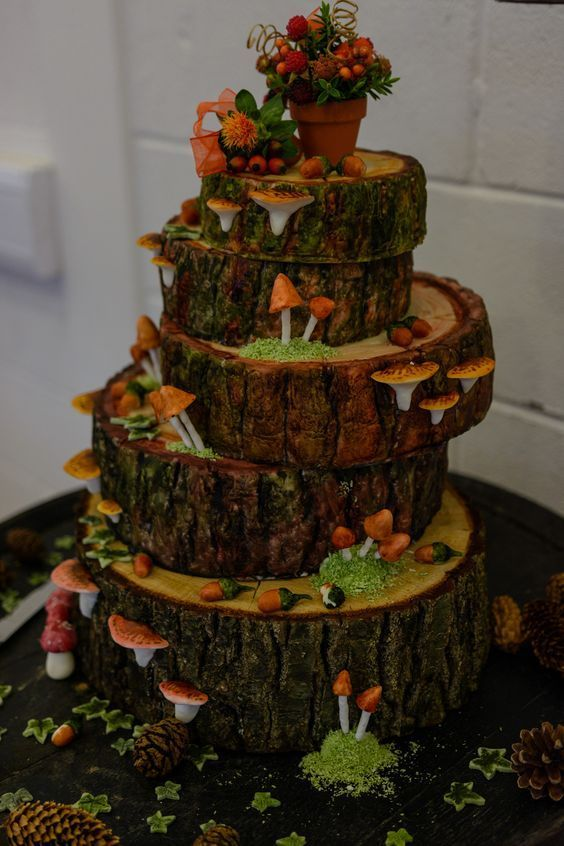 a whimsy wedding cake done as tree slices, with sugar acorns, mushrooms, moss and berries on top