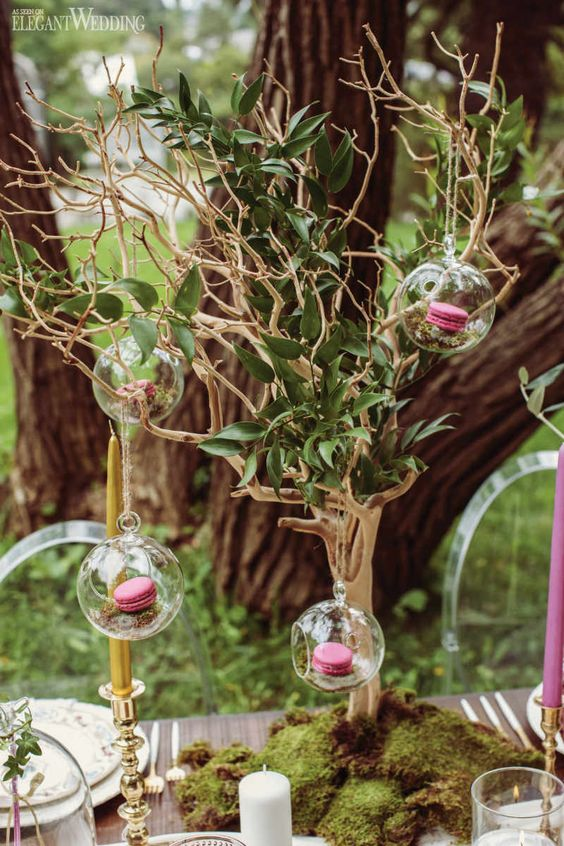 a whimsy woodland wedding centerpiece of a tree with foliage, glass bubbles with moss and pink macarons